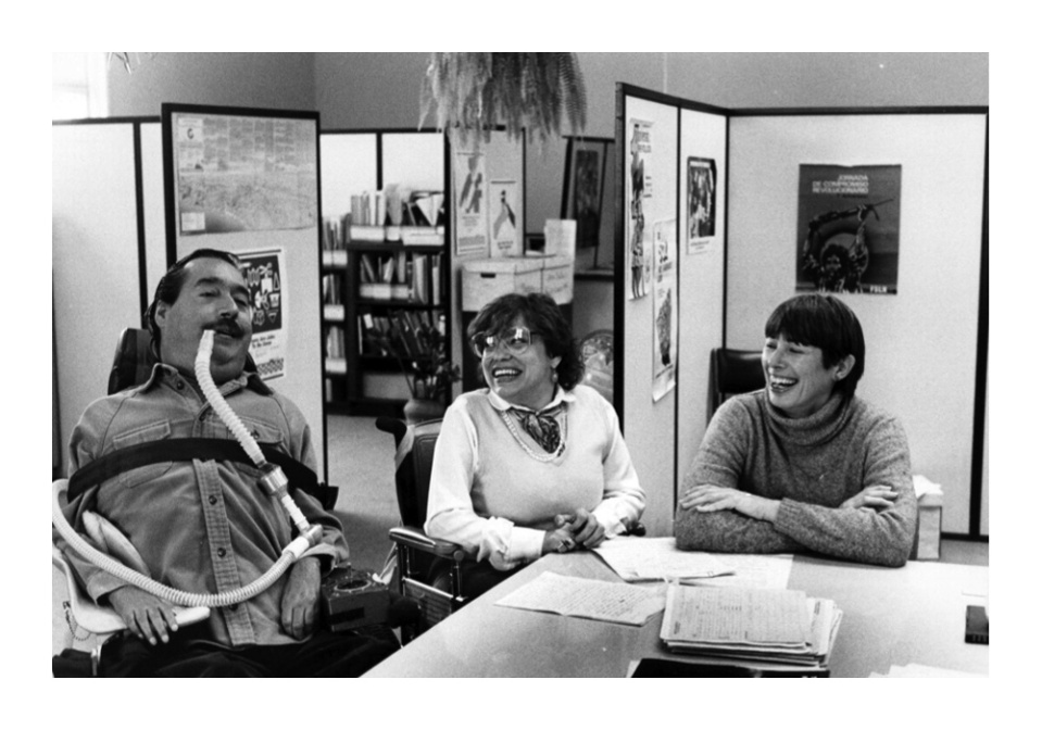 Black and White photo of the three founders of the World Institute on Disabilty (WID) in an office setting. Judy Heumann and Joan Leon turn to Ed Roberts and laugh. Ed and Judy are using wheelchairs, and Ed uses a portable ventilator.