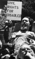 "Black and white photo shows Ed Roberts as a young man in his power wheelchair in an outdoor setting with a man in the background holding a sign that says ""Civil rights for the disabled.""Image result for Ed Roberts"
