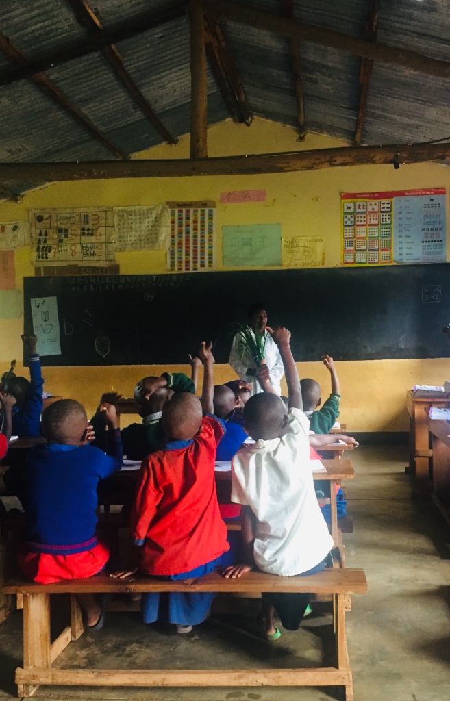 Children in a classroom with hands raised responding to their teacher.